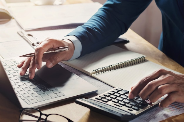 Geschäftsmann workig und mit taschenrechner mit laptop auf schreibtisch