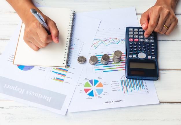 Geschäftsmann writing auf notizbuch mit dem zählen des geldes und analysieren des investitionsdiagramms im offi