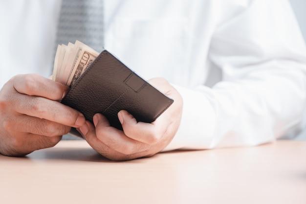 Geschäftsmann zählt banknoten in seiner brieftasche.