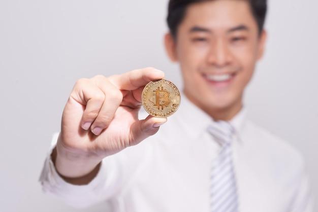 Geschäftsmann zeigen bitcoin-goldmünze. zuversichtliche neuinvestition in den digitalen währungsumtausch und weltweite zahlungen.