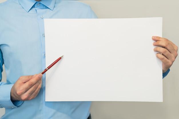 Geschäftsmann zeigt auf leerem weißem blatt