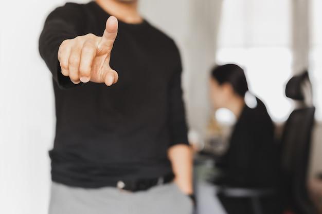 Geschäftsmann zeigt finger mit frau, die im hintergrund arbeitet.