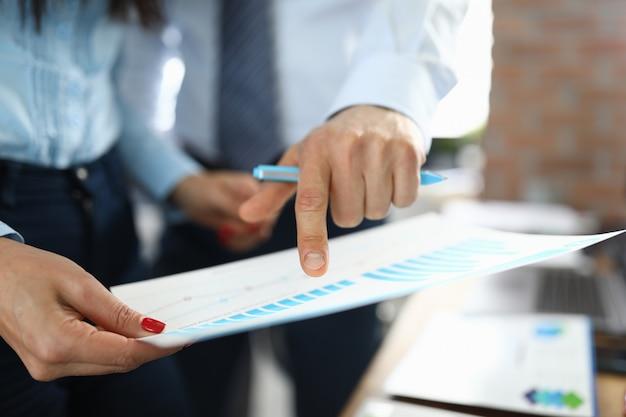 Geschäftsmann zeigt geschäftsleistung auf graph nahaufnahme