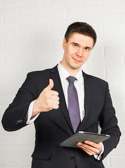 Geschäftsmann zeigt ok-zeichen mit dem daumen nach oben.