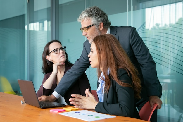 Geschäftsmann zeigt präsentation auf pc zu mitarbeitern.