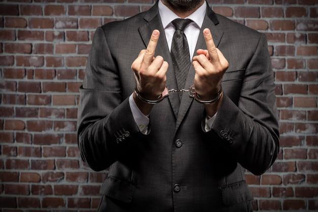 Geschäftsmann zeigt seinen mittelfinger mit einer handschelle in einem gefängnis. konzept der korruption, korrupte politiker, illegale unternehmen. backsteinhintergrund.