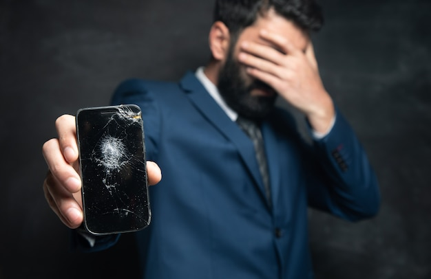 Geschäftsmann zerschmetterte smartphonebildschirm auf dunkler oberfläche