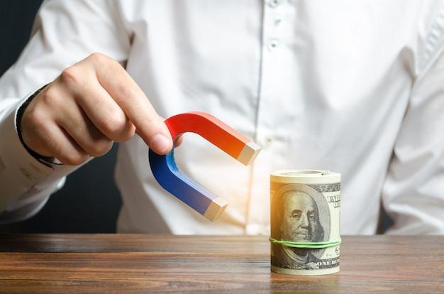 Geschäftsmann zieht geld mit einem magneten an. geld und investitionen für geschäftliche zwecke anziehen