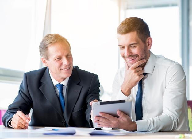 Geschäftsmann zwei, der unter verwendung der digitalen tablette sich bespricht