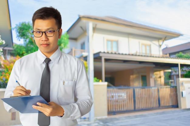 Geschäftsmannabnutzungsgläser und tragendes anzugsschreiben auf notizblock oder klemmbrett
