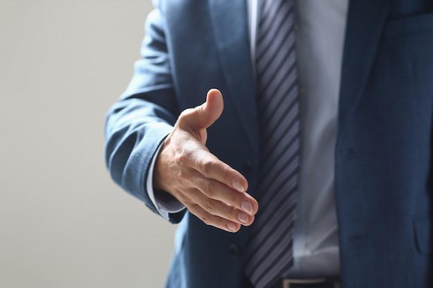 Geschäftsmannangebothand, zum als hallo in der büronahaufnahme zu rütteln
