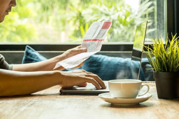 Geschäftsmannarbeit über den laptop, der rechnung mit kaffee auf holztisch überprüft