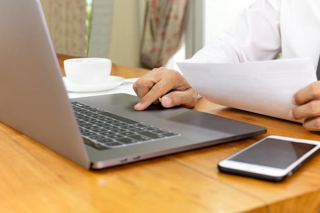 Geschäftsmannarbeit über laptop analysieren aktienbericht im beschneidungspfad