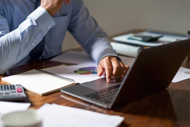 Geschäftsmannarbeitsscheckbuchhaltungsbericht über laptop im büro.
