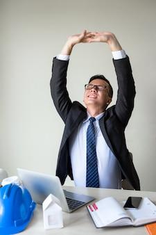 Geschäftsmannausdehnungshände, zum von rückenschmerzen zu entlasten