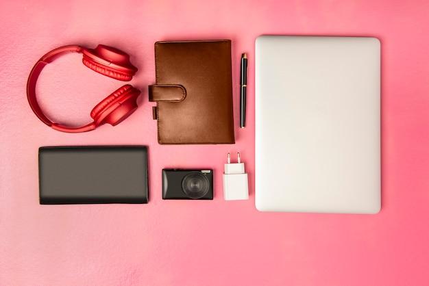 Geschäftsmannausrüstung wie laptop, stift, notizbuch, kamera, geldbörse und kopfhörer für arbeit