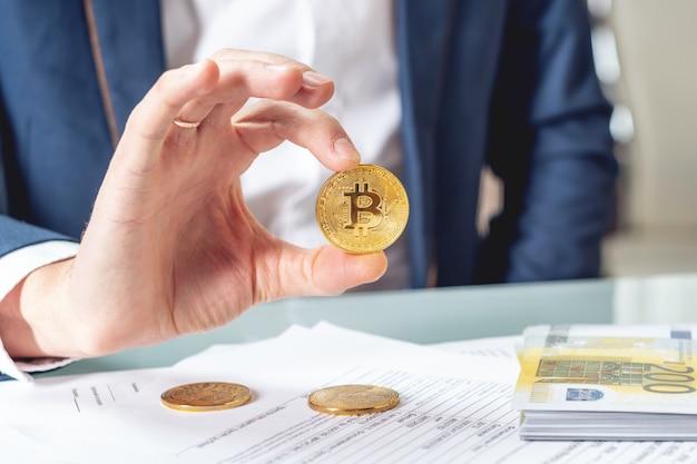 Geschäftsmannbanker, der bei tisch mit den papieren halten ein münzenbitcoin sitzt. umtausch und verkauf von kryptowährung