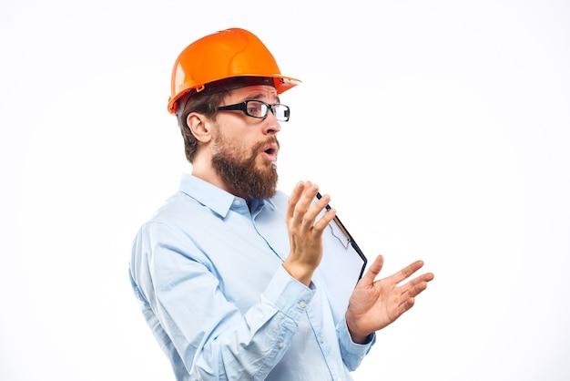 Geschäftsmannbau-schutzhelm mit professionellen industriedokumenten.
