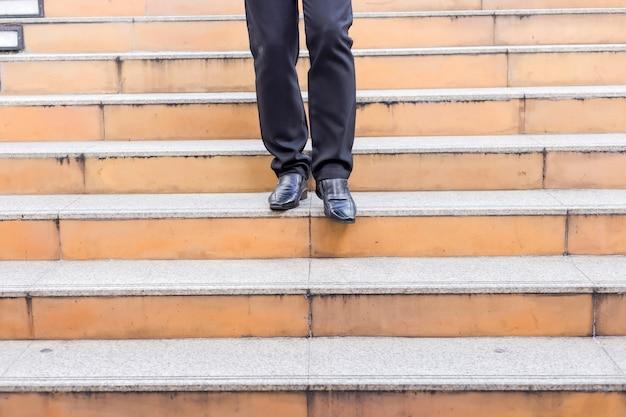 Geschäftsmannbeine, die schritt auf einem niedrigeren niveau auf treppe - schlechtes anlagenentscheidungskonzept unternehmen