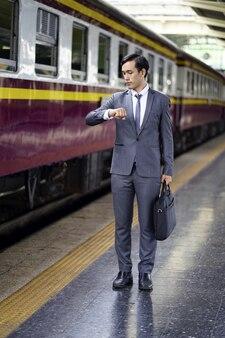 Geschäftsmannblick auf armbanduhren und wartende untergrundbahn. schöner mann in anzug und tasche s
