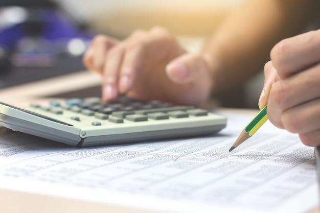 Geschäftsmannbuchhalterhand, die den bleistift arbeitet an dem taschenrechner hält, um finanziell zu berechnen