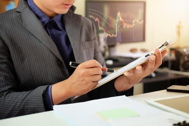 Geschäftsmanncheckliste auf diagrammbrett mit finanzkonzept.
