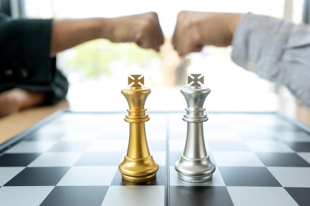 Geschäftsmannfauststoß nahe dem schachbrett mit den silbernen und goldenen schachfiguren