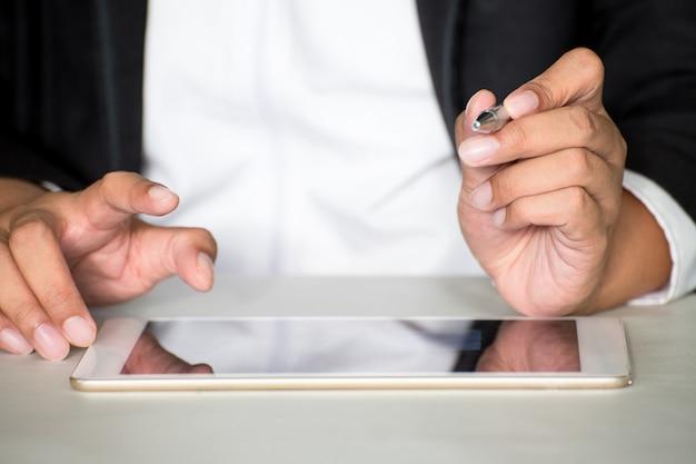Geschäftsmannforschungsinformationsnotizbuch-tablettenhandy im büro.