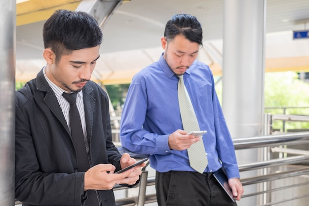 Geschäftsmanngebrauch mit zwei jungen asien des intelligenten telefons