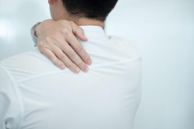 Geschäftsmanngefühlsschmerz in ihrem zurück beim arbeiten im büro, medizinisches konzept