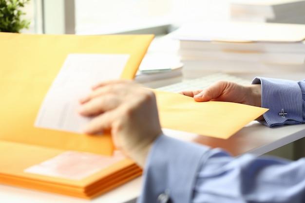 Geschäftsmanngriffhandgelb-postumschlag