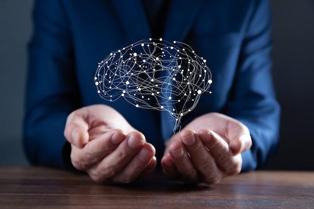 Geschäftsmannhände, die abstraktes polygonales gehirn auf dunkelheit halten
