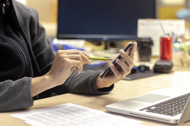 Geschäftsmannhände, die bleistift und smartphone mit laptop-computer und finanzbericht halten