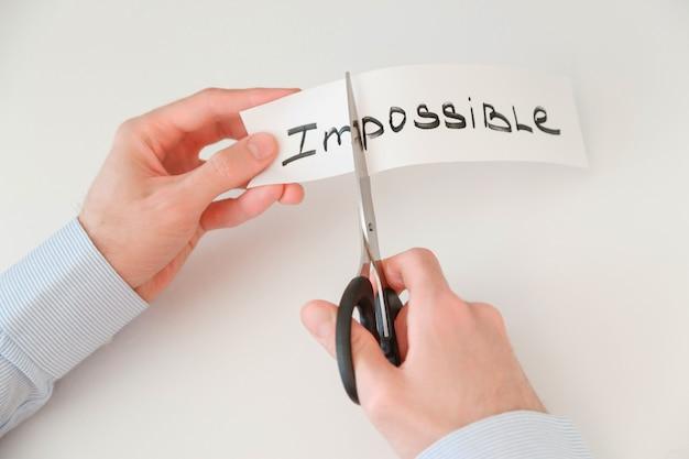 Geschäftsmannhände, die das wort unmöglich schneiden