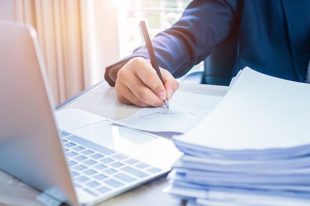 Geschäftsmannhände, die daten in computer, stapel papierdateien für das suchen bearbeiten und schreiben