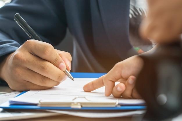 Geschäftsmannhände, die daten, stapel papierdateien für das suchen von informatio bearbeiten und schreiben