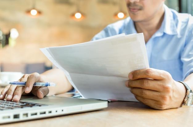 Geschäftsmannhände, die dokumentenschreibarbeit und -stift arbeiten an laptop halten.