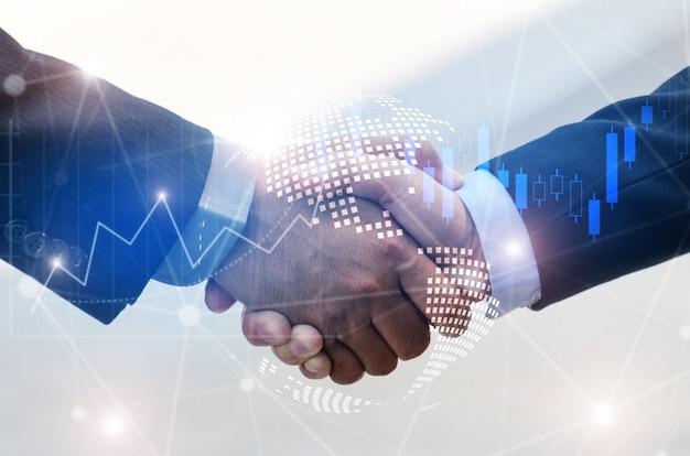 Geschäftsmannhändedruck mit effektdiagramm des devisenmarktes und des grafischen hologramms der globalen weltkartennetzverbindung
