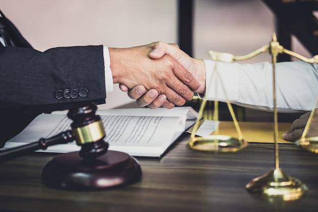 Geschäftsmannhändedruck mit männlichem rechtsanwalt, nachdem viel vertrag besprochen worden ist