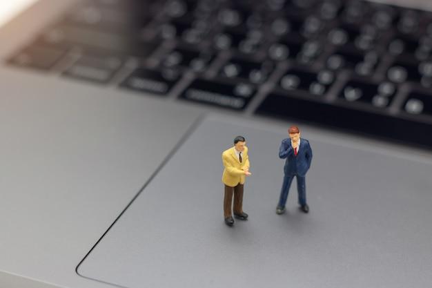 Geschäftsmannhändedruck zum geschäftserfolg online auf laptop.