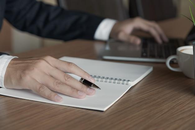 Geschäftsmannhand, die an einem computer arbeitet und auf einen notizblock mit einem stift in das büro schreibt