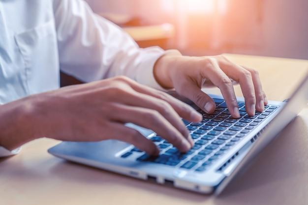 Geschäftsmannhand, die auf computertastatur eines laptops im büro tippt. geschäfts- und finanzkonzept.