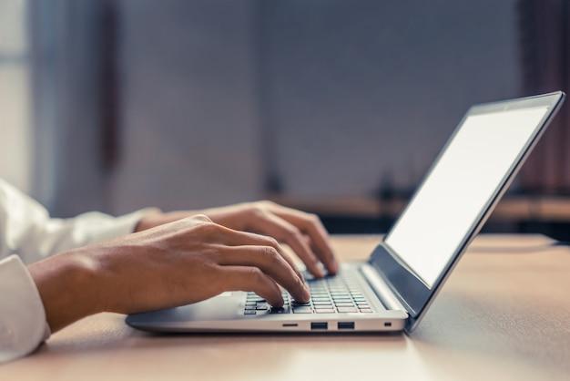 Geschäftsmannhand, die auf computertastatur tippt