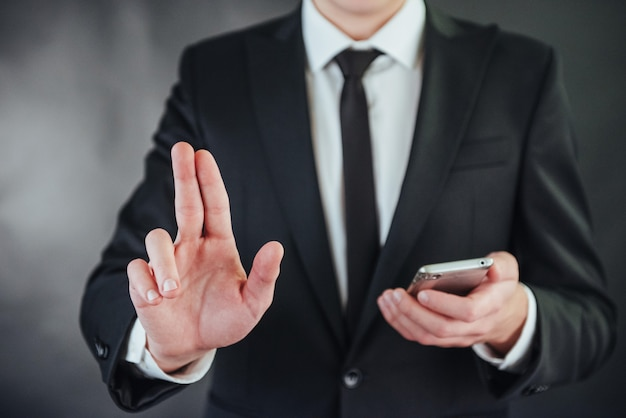Geschäftsmannhand, die auf leeren raum auf schwarzem hintergrund zeigt