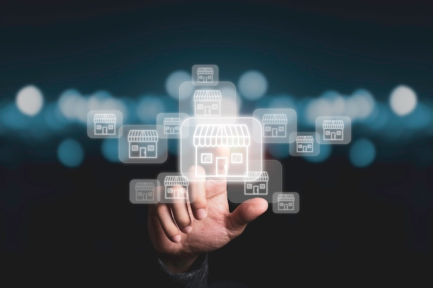 Geschäftsmannhand, die auf virtuelles einkaufsgeschäft zeigt, das verbindungslinie mit anderen kleinen einkaufsgeschäften, erweitert und entwickelt franchise-konzept.