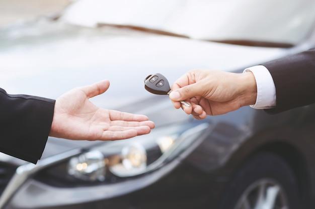 Geschäftsmannhand, die autoschlüsselfront mit neuem auto hält, parkplatz vor dem haus. transportkonzept.