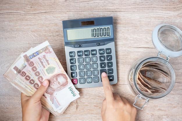 Geschäftsmannhand, die banknotenstapel des thailändischen baht hält und taschenrechner verwendet.