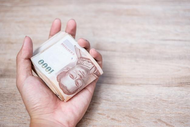Geschäftsmannhand, die banknotenstapel des thailändischen baht hält.