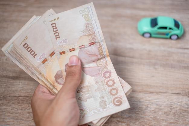Geschäftsmannhand, die banknotenstapel des thailändischen baht mit auto hält.