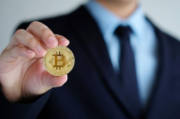 Geschäftsmannhand, die bitcoins, abschluss, kryptowährung und blockchain konzept hochhält